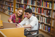 Picture of two younger people working in a library on a computer - one uses a wheelchair