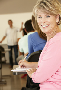Picture of Older woman in a classroom looking back over her shoulder at you at a desk