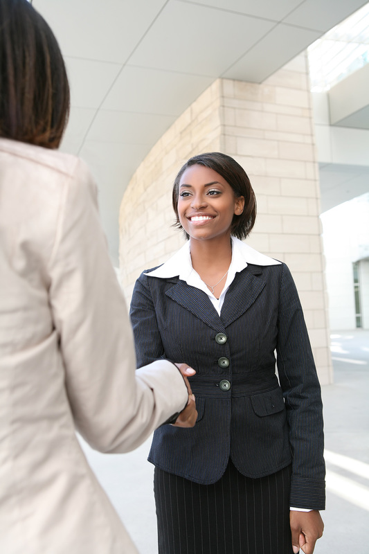 photo of two professionally dressed African American women shaking hands