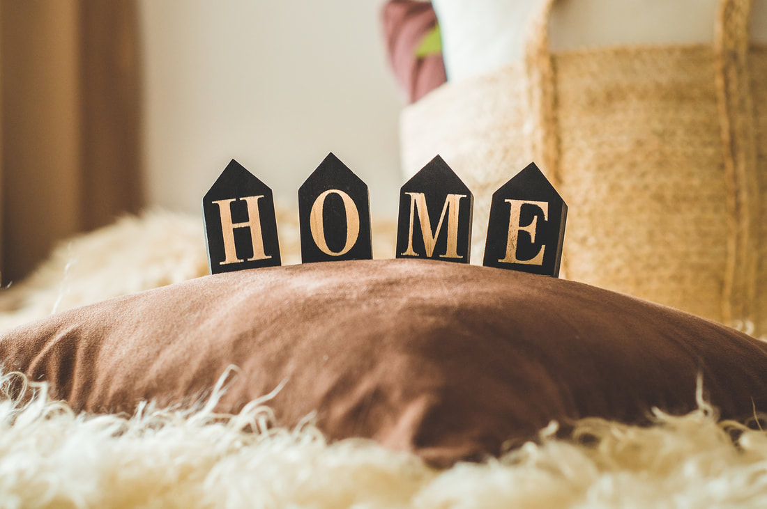four small house-shaped plaques spelling out HOME