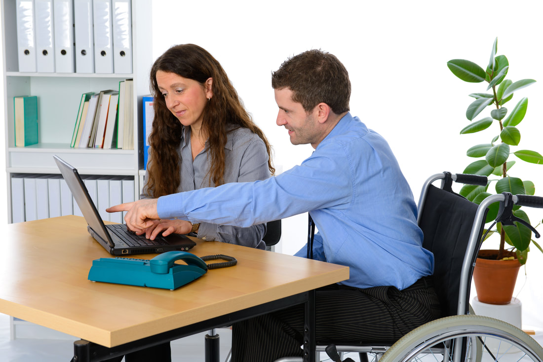 A man in a wheelchair is looking at a laptop with a female co-worker