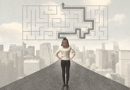 A woman stands looking at a maze with a path through it.