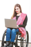 Young Latina in a wheelchair looking at her laptop